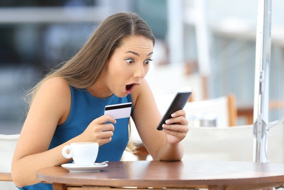 young woman at table with credit card in one hand, looking in amazement at cell phone, mouth open
