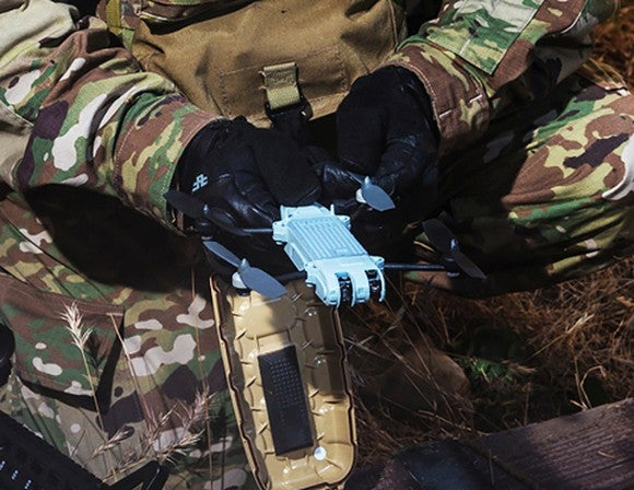Small handheld drone in a military person's hand.
