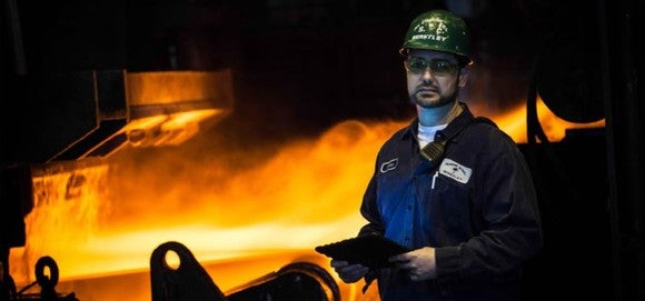 Nucor employee in front of a steel mill.