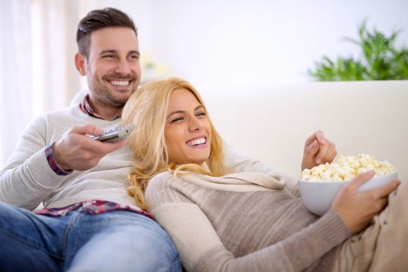 A smiling couple relaxing on a couch, with popcorn and TV remotes close at hand.