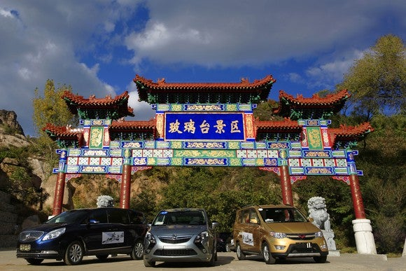 General Motors vehicles in front of Chinese architecture