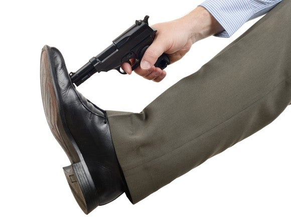 A man pressing a revolver against his shoe as if to shoot it