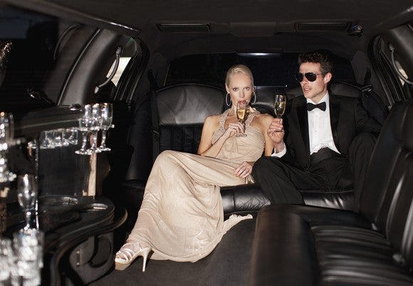 A couple sips champagne inside an elaborate limousine, with a bar laid out next to their seat.