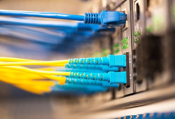 Several Ethernet and fiber optic networking cables, plugged into a large-scale networking switch.