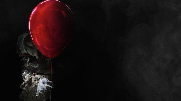 "Pennywise, the villain clown from ""It,"" holding a red balloon."