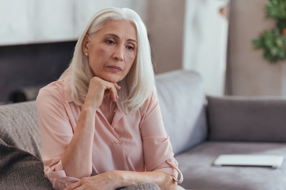 Older woman seated with hand under her chin in seemingly deep thought