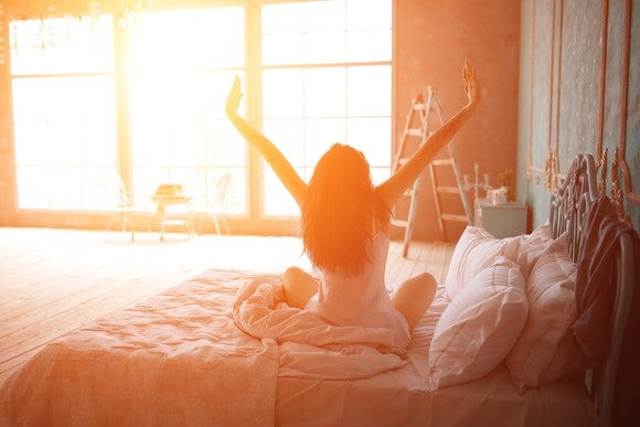 With sun pouring in from a window across the room, a woman with her back to the camera sits up in bed with her arms raised, as if stretching.