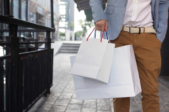 A man holding shopping bags while walking down the street.
