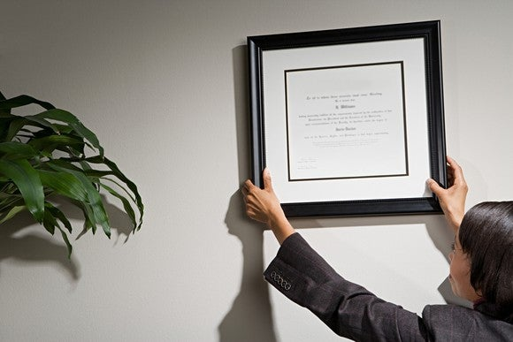 Woman hanging framed certificate on wall