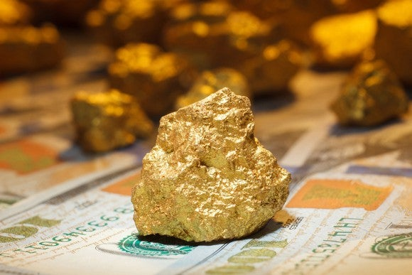 A big gold nugget on $100 bills.