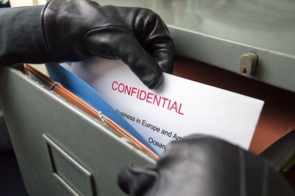 A man steals confidential documents from a filing cabinet.