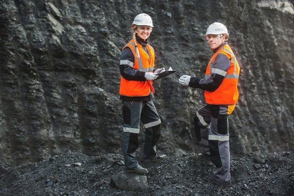 A man and a woman stand in front of a seam of coal at a site that's being strip mined.
