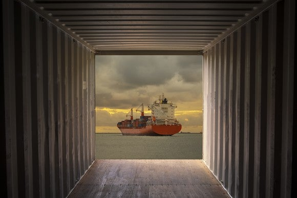 A cargo container ship sailing out of view from a cargo container.