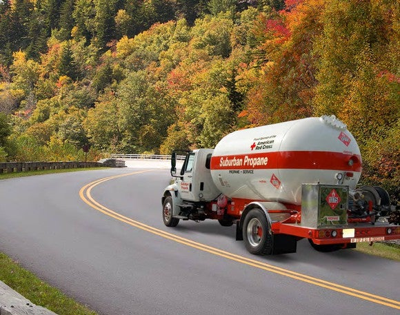 A truck with the Suburban Propane and American Red Cross logos on its side, driving down a two-lane road bordered by fall-leaved trees