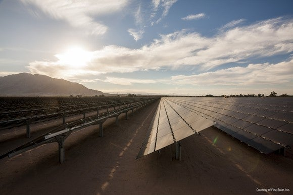 Large solar installation in the desert with the sun in the background.