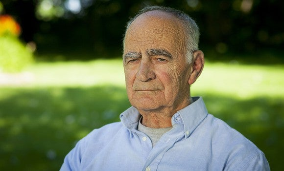 An elderly man sits outdoors with a concerned expression.