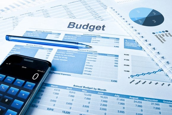 A budget laid out on a table next to a pen and a smartphone.