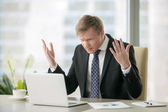 A man in a suit, sitting at a desk, looks at a computer with both hands up in the air in frustration.