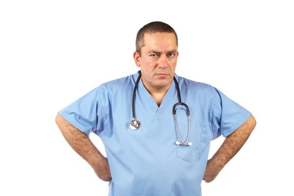 An angry doctor with his hands on his hips.