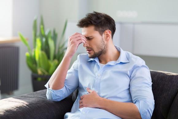 Man pinching his nose to indicate headache