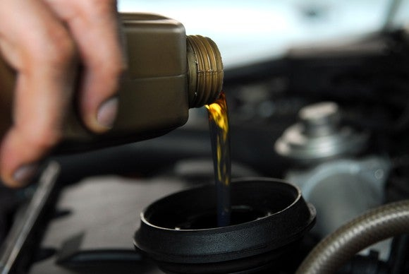 A hand pouring motor oil into a car's engine