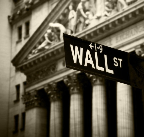 Wall Street street sign in front of the New York Stock Exchange.
