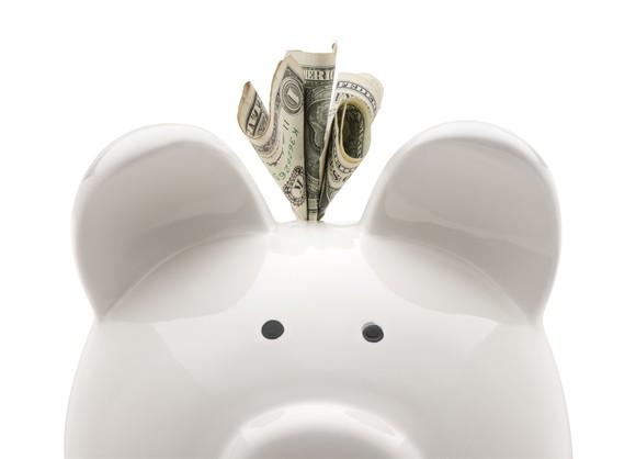 Dollar bill sticking out of piggy bank