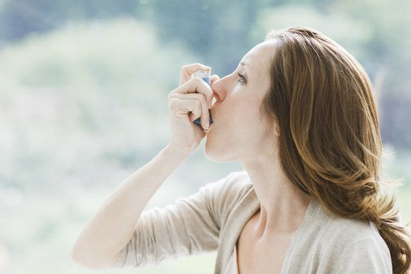 A woman with asthma using a rescue inhaler.