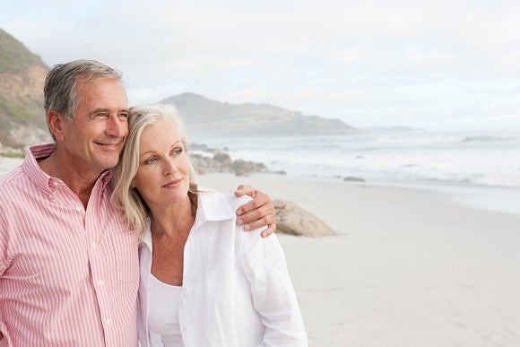Older couple on a beach, looking at the ocean.
