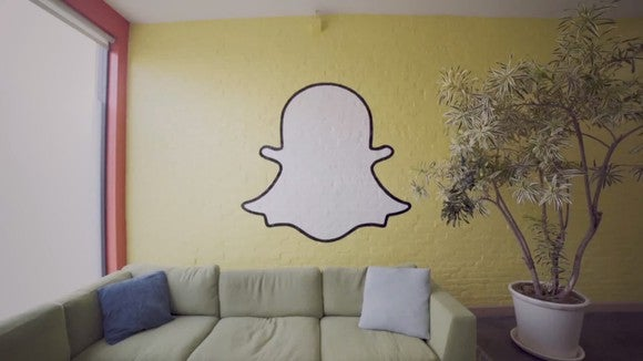 Yellow wall decorated with a white Snapchat ghost. A green couch and a potted plant can also be seen.