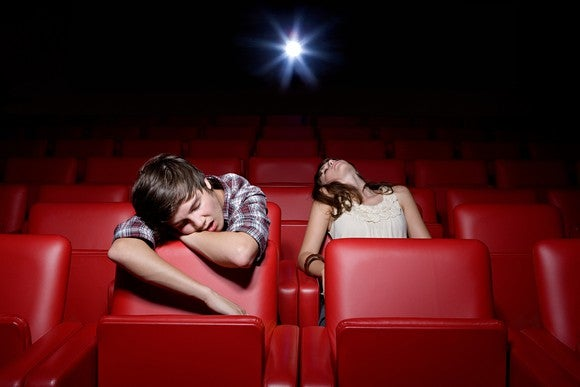 Two young people, one boy and one girl, falling asleep in the red seats of an otherwise empty movie theater.