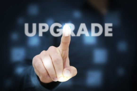 "A person pointing to the word ""upgrade"" on a screen."