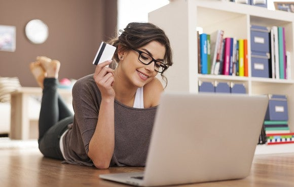 A woman lies on the floor in front of a laptop, smiling with a credit card in hand.