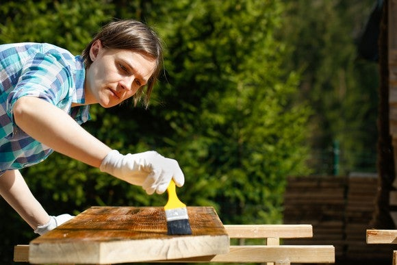 Woman staining wood
