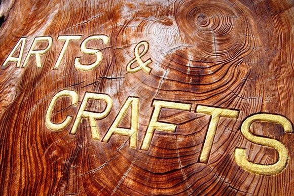 "The words ""Arts & Crafts"" embossed in gold letters on a deeply textured slab of dark wood."