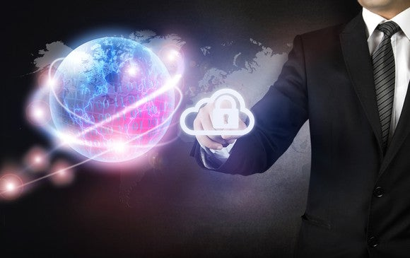 Businessman holding out his hand towards a digital image of a glowing Earth, surrounded by strands of brighter lights. Between his fingers, he holds a digital icon of a padlock inside a cloud.