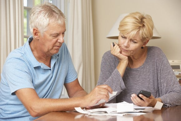 Older couple reviewing papers at a table, looking serious