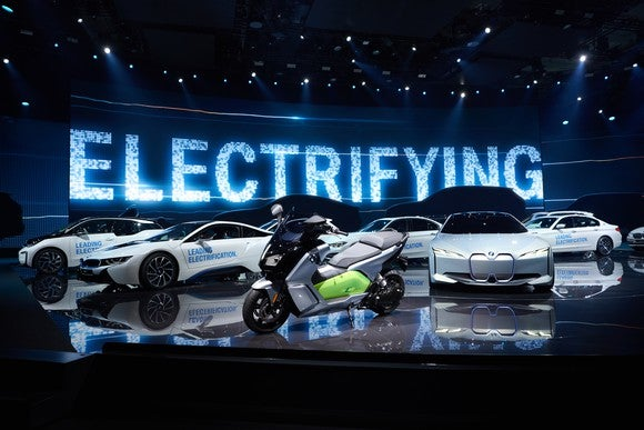 "The i Vision Next is shown parked on a show stand, with other BMWs -- including an electric motorcycle -- parked nearby. The word ""electrifying"" appears on a big screen in the background."