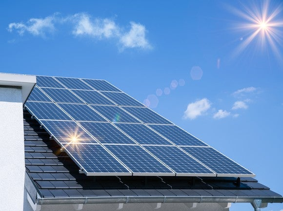 A solar installation on a rooftop with the sun in the background.