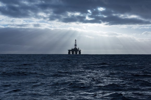 Offshore drilling rig with sun rays coming through the clouds.