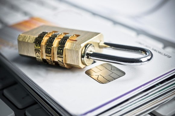 Combination lock on top of a stack of credit cards.