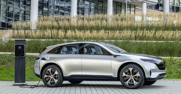 The Mercedes-Benz Generation EQ Concept, a silver SUV, next to a recharging station.