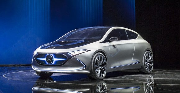 The Mercedes-Benz Concept EQA, a silver hatchback with a distinctive lighted Mercedes badge in front, on its auto-show stand in Frankfurt.