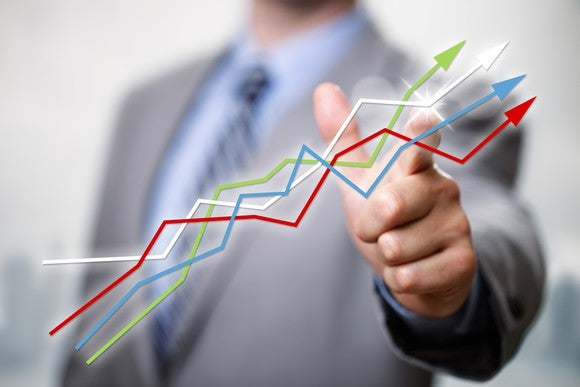 A man in a suit points to a grouping of lines -- green, white, blue, and red -- going upward, as if following a stock chart.