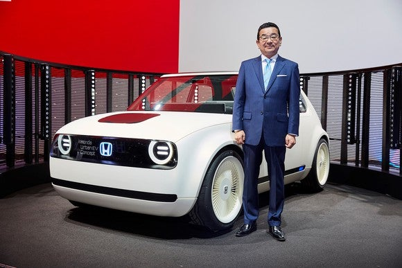 Hachigo is standing next to the Urban EV Concept, a small white hatchback, on Honda's stand at the International Motor Show in Frankfurt.