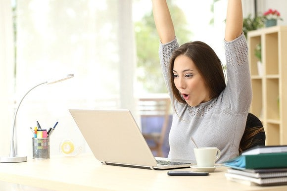 Woman excited at what she sees on her laptop screen