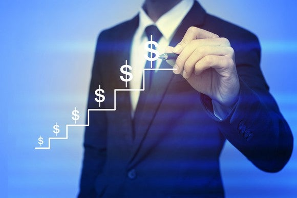Business man holding pen up to drawing of steps with dollar symbols