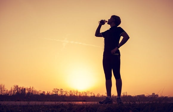 Runner stopped to drink water with sun on horizon in background