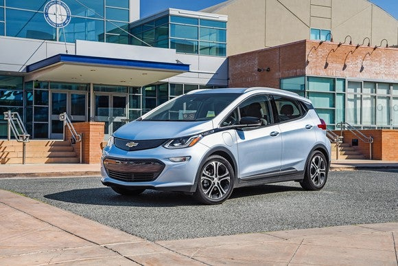 A Chevrolet Bolt EV parked in front of a public building.