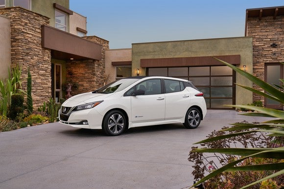 A white 2018 Nissan Leaf parked in a residential driveway.